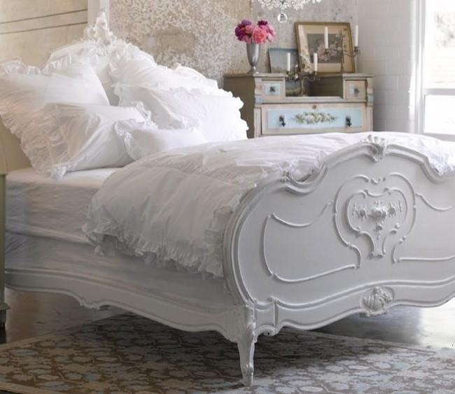 Роскошная кровать из дерева с резными быльцами и ножками, а также старинного вида прикроватная тумба - мебель, характерная для стиля шебби