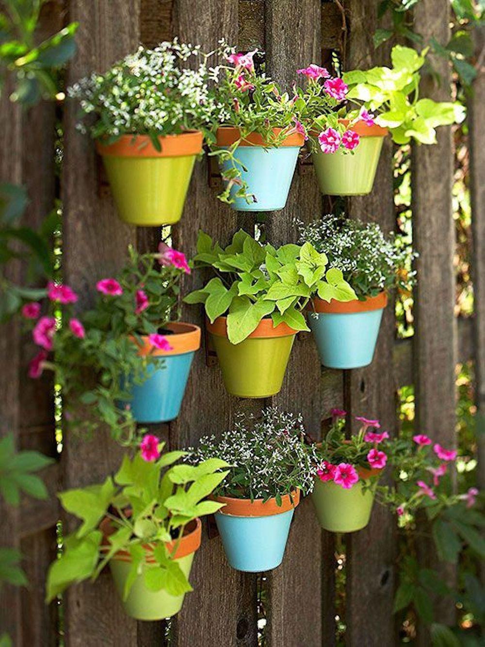Небольшие пластиковые горшочки с цветами украсят забор на даче