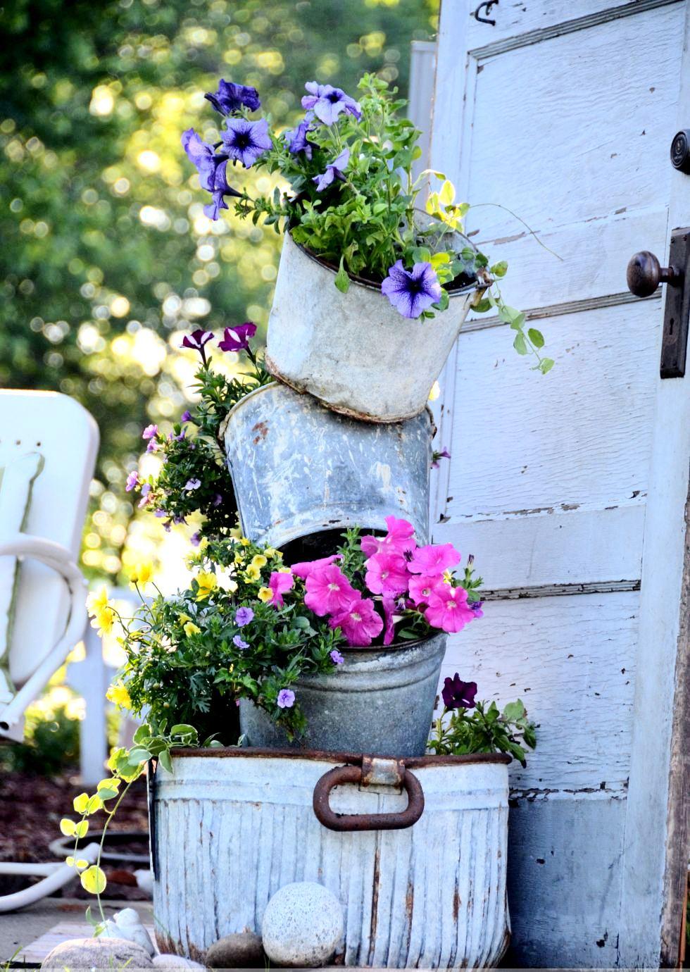 Для кого-то старые ржавые ведра это мусор, а кого-то привлечет идея создать из них вазоны для цветов в форме вертикальной композиции