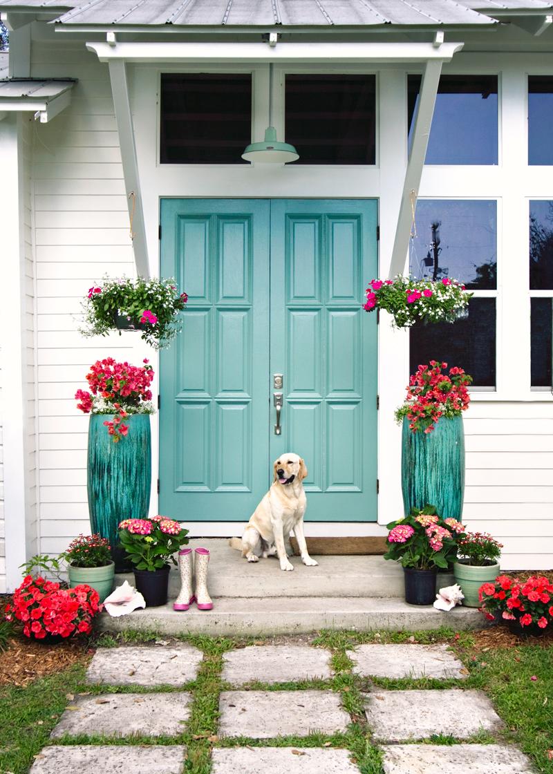 Создать красоту вокруг главного входа помогут подобранные в общую цветовую гамму высокие горшки с цветами