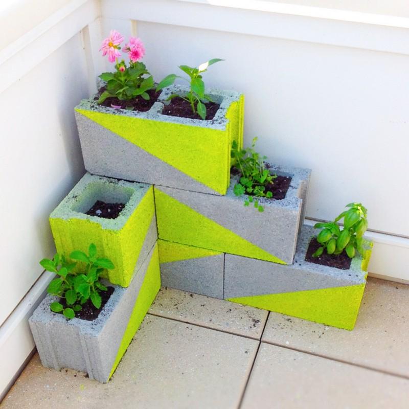Бетонные блоки тоже можно использовать в качестве вазона для цветов, применив для них яркую раскраску они станут незаменимым элементом декора