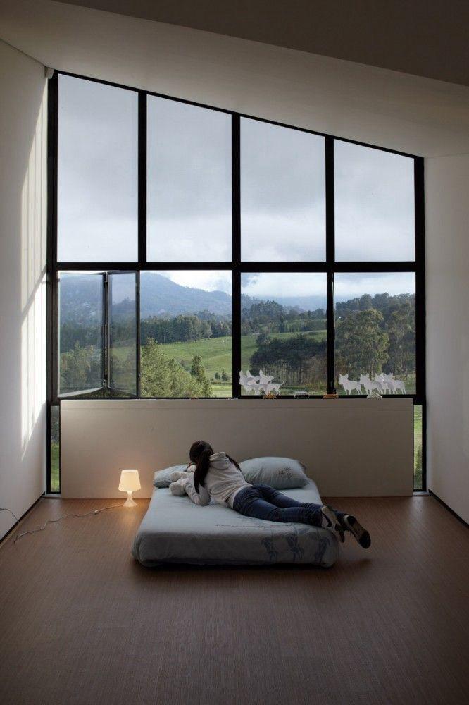 Спальня дома с витражным остеклением фасада с видом на горы