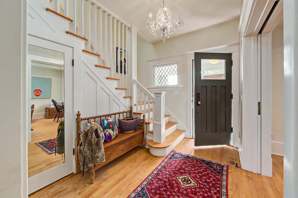 Удобное место возле лестницы занимает деревянная банкетка, которая сможет приютить ваши сумки