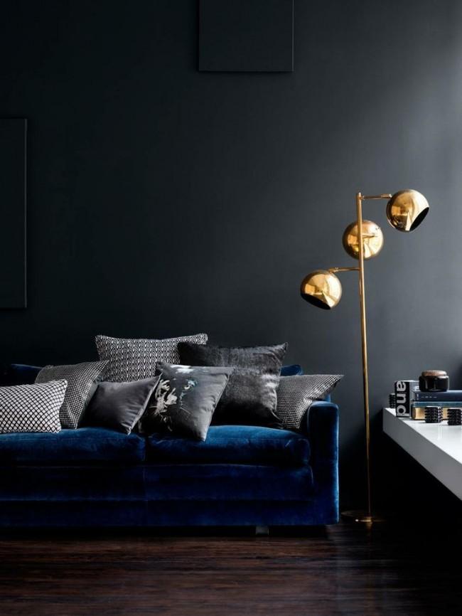 Роскошный синит бархат дивана выглядит очень солидно на фоне черной стены. Золотой светильник придает комнате изысканности