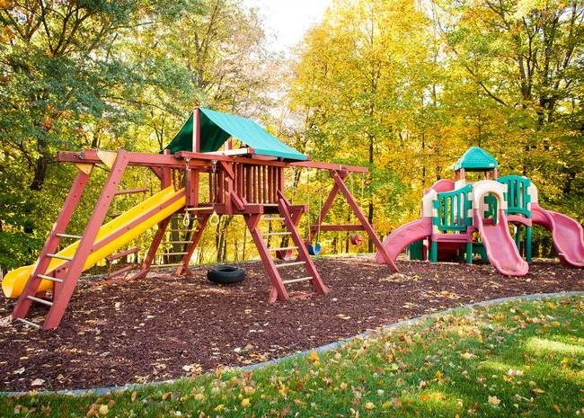 Яркая детская площадка очень красиво смотрится на фоне осенней листвы