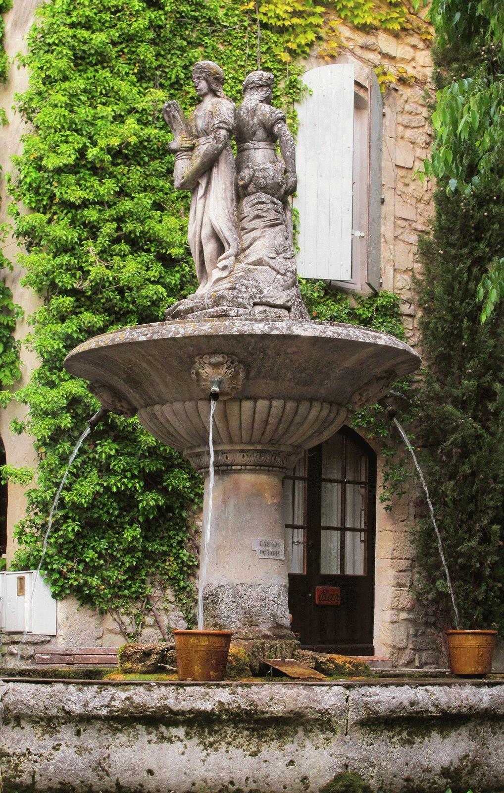 Скульптуры на фонтане в классическом саду