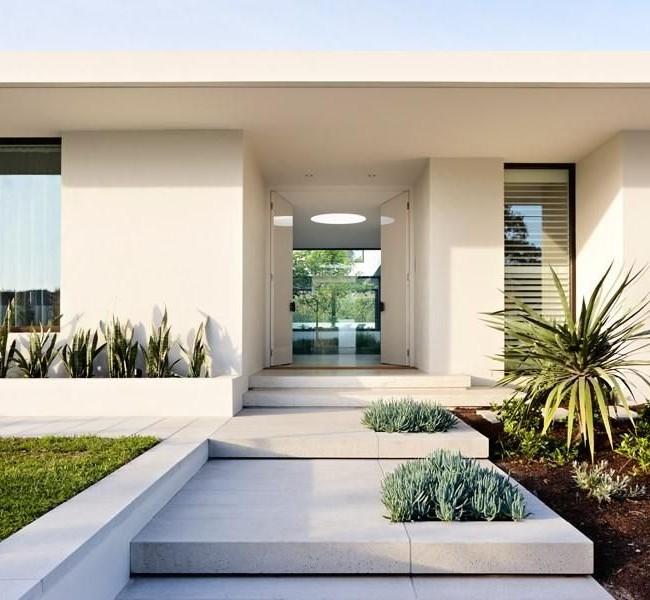 Бетонный вход белого цвета идеально дополняет фасад дома