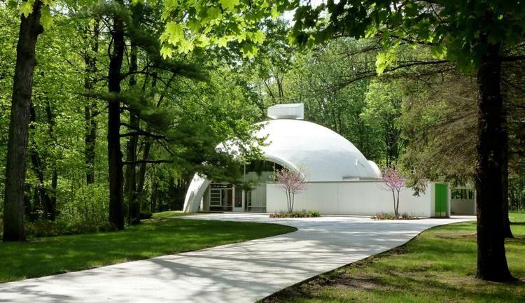Белый купольный дом среди густой зелени