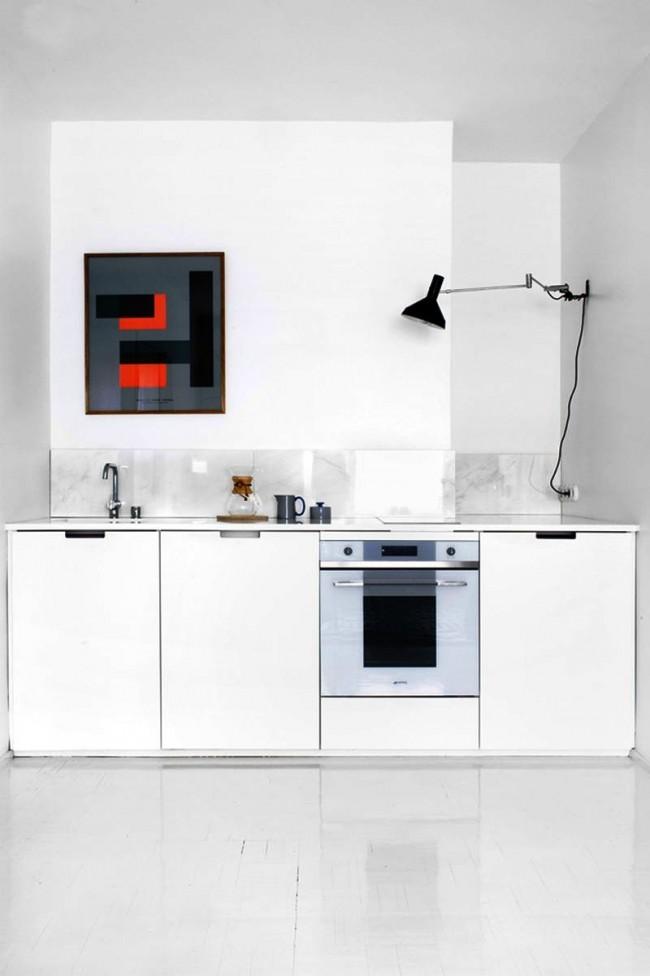 Постер с геометрическим рисунком в темных тонах на белой кухне