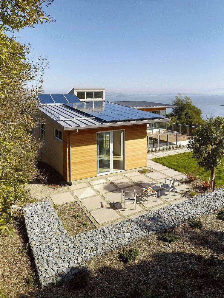 На плоской крыше небольшого дому установлены солнечные батареи