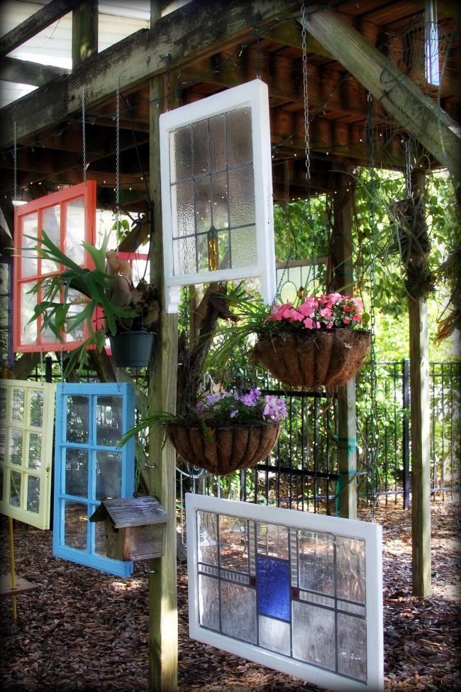 Необычную композицию можно создать при помощи разноцветных старых окон и кашпо с цветами