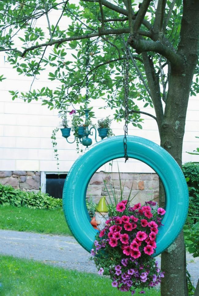Кашпо для цветов из шины, подвешенной вертикально к дереву, - простой и эффектный способ украсить территорию дома
