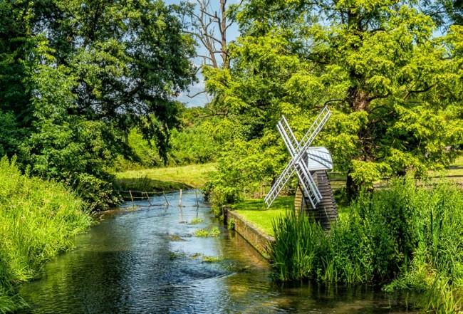 Эффектно смотрится декоративная мельница в живописном ландшафте на берегу реки