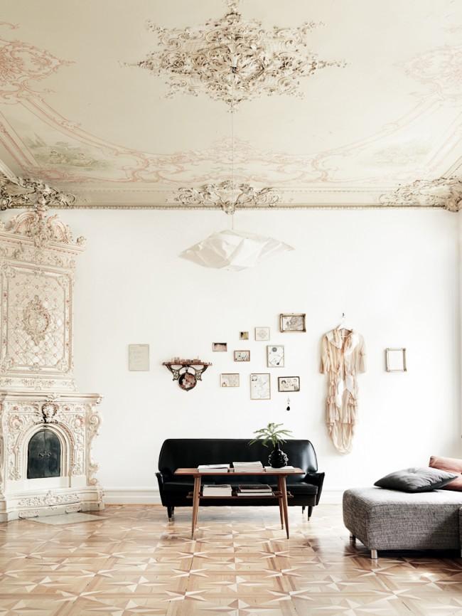 Светлые стены, высокие потолки и пол из дорогих пород дерева в неоклассическом интерьере