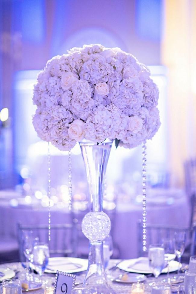 Благородно смотрятся на столах для гостей очень высокие хрустальные вазы с пышными цветочными композициями