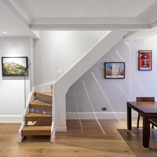 Необычная лестница со стеклянными перилами в модерновом интерьере