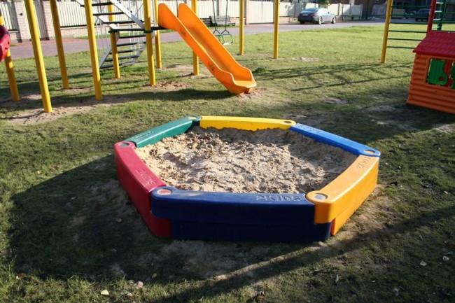 Песочница из линейного полиэтилена на игровой лужайке