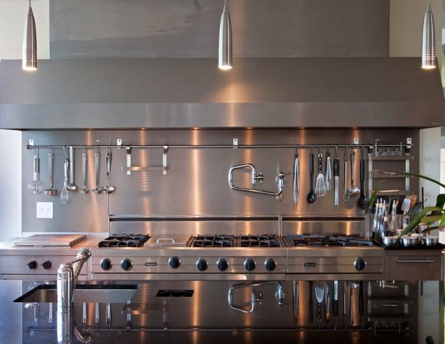 Длинный алюминиевый рейлинг на кухне со шкафами, фартуком и рабочей поверхностью преимущественно из шлифованного металла