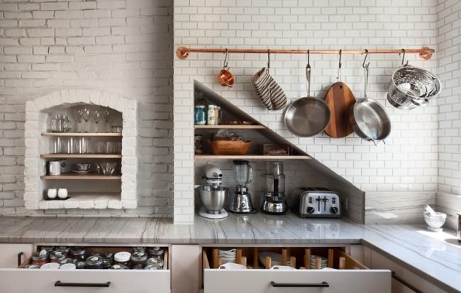 Бронзовый рейлинг, несущий в том числе декоративную функцию на белой кирпичной стене кухни