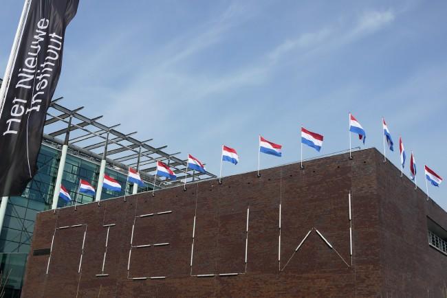 На крыше выставочного павильона четырнадцать голландских флагов.