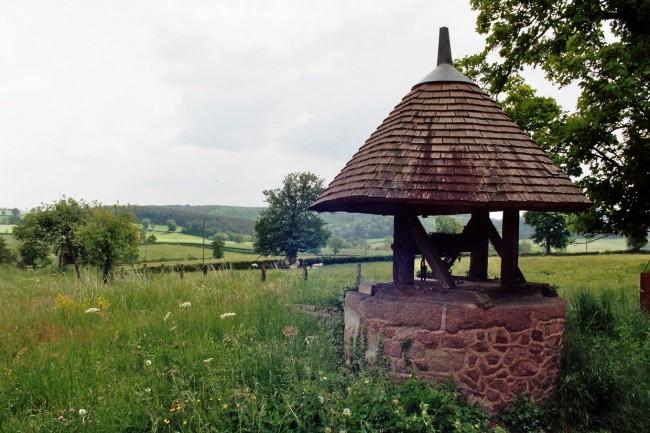 Красивый домик для колодца с крышей в форме конуса