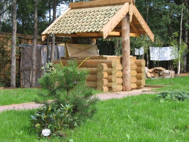 Красивый деревянный домик для колодца с резными элементами