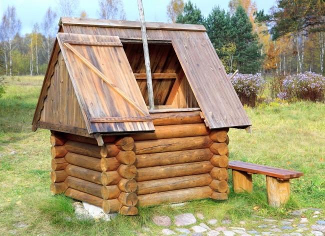 Домик для колодца в виде четырехугольного сруба и оформленной крыши