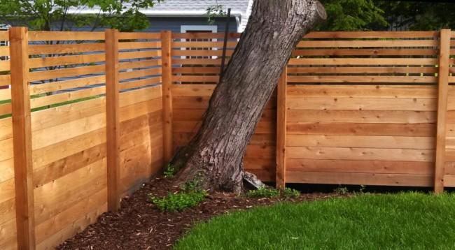 Деревянные заборы и ограждения для дома. Один из распространенных способов организовывания приватного пространства двора: доски нижней части деревянного забора плотно подогнаны друг к другу, верхние - дают двусторонний обзор