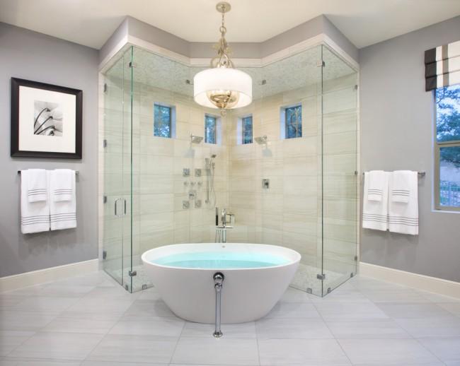 Душевые ограждения из стекла без поддона. Бескаркасные душевые кабины устанавливаются прямо на пол ванной. На фото - душевой бокс необычной конфигурации, выстроенный вокруг ванны, многоугольный и с двумя входами