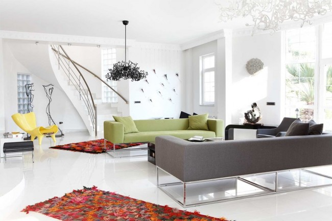 Ковры в интерьере гостиной. Минималистичную отделку гостиной в белых тонах превосходно уравновешивают яркие цветовые пятна, например, ковры ручной работы