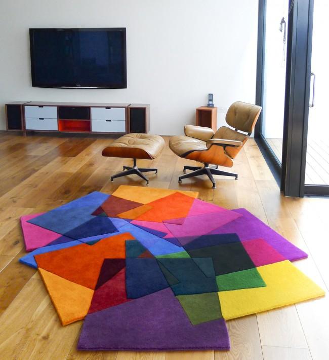 Яркий ковер неправильной формы может быть единственным акцентом в гостиной, оформленной в строгих геометричных мотивах и неброских тонах