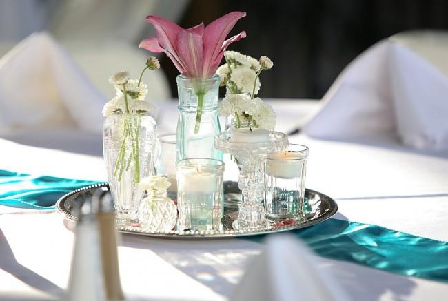 Сервировка стола в домашних условиях. Вполне допустим многочисленный мелкий декор стола. Лучше всего группировать его зрительно вокруг раннера, или возможно, даже лент, перекинутых вдоль или поперек стола