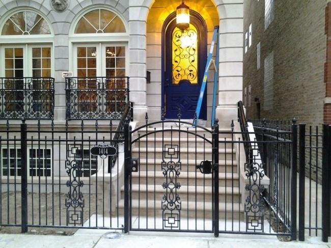 Кованый забор гармонично сочетается с такими же ограждениями на окнах и коваными элементами дверей