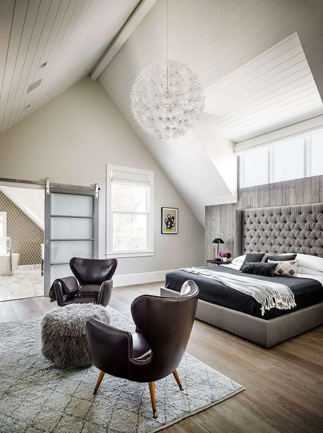 Уютная современная спальня с просторной кроватью и шикарными кожаными креслами
