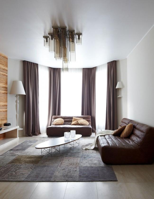 Белый натяжной потолок поможет подчеркнуть строгость гостиной комнаты