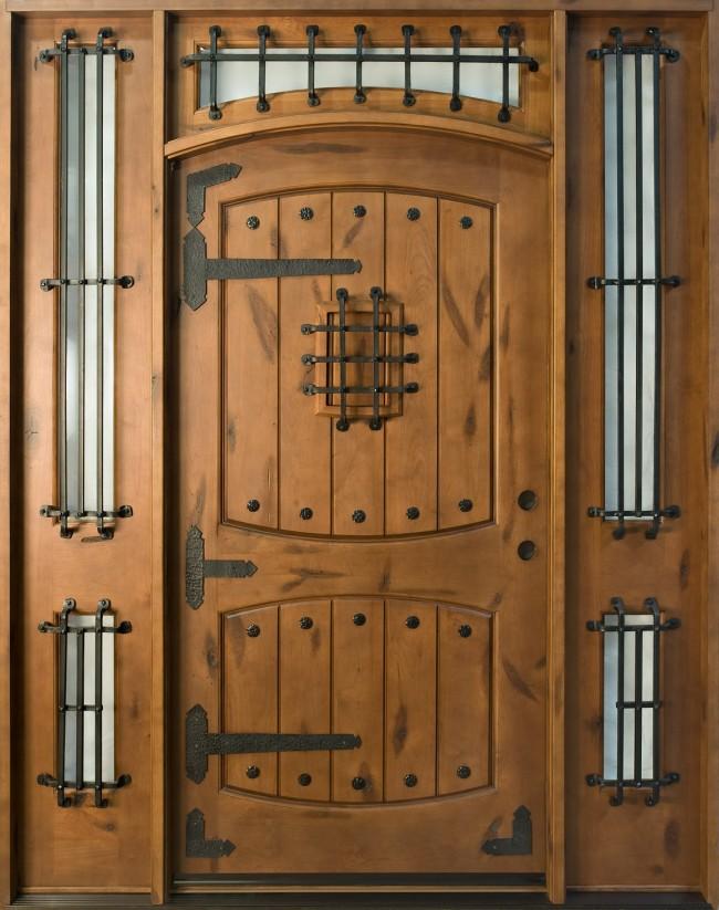 Лучшие входные двери в частный дом. Тяжеловесные деревянные двери с металлическими решетками - хороший выбор для кантри- или средневекового стиля оформления усадьбы