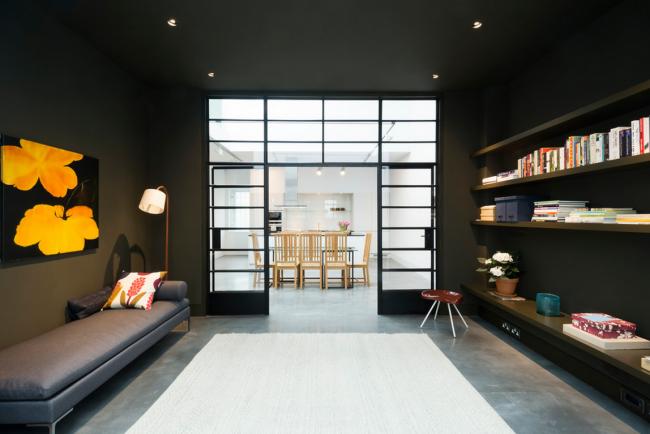 Интерьер гостинной в серых тонах разработанный Тео Оттеном с помощью стеклянных дверей плавно отделяется от светлой столовой