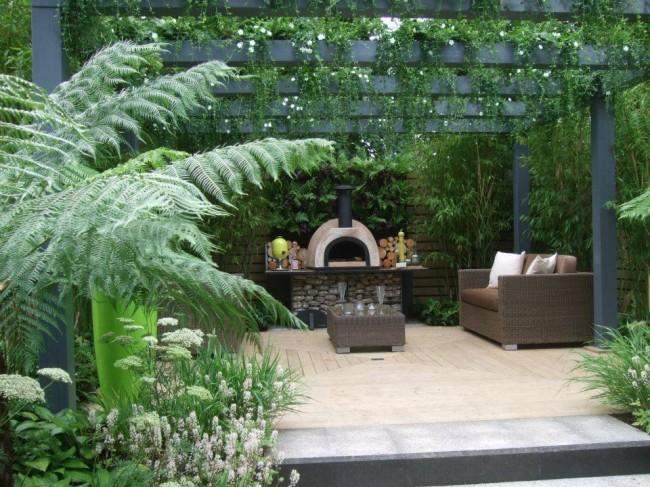 Пергола с камином-печью, утопающая в зарослях растений и цветов