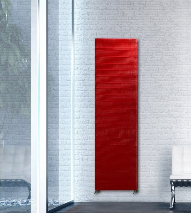Красный радиатор панельного типа смотрится очень эффектно на белой стене