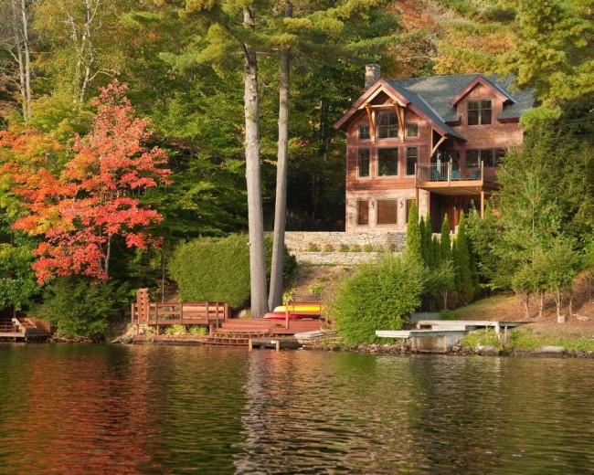 Великолепный вид каркасного дома на фоне леса и озера