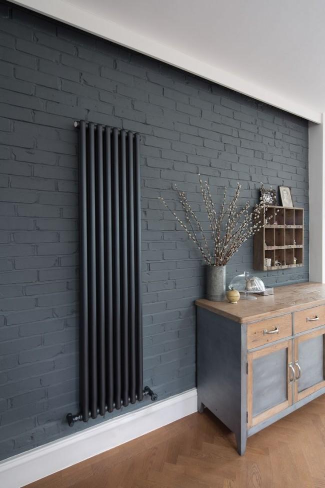 Черный радиатор на фоне серой кирпичной стены