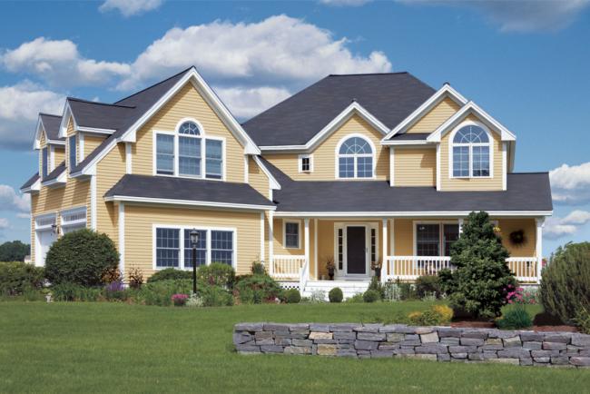 Благодаря яркому цвету сайдинга дом станет выгодно выделяться на фоне зеленых насаждений