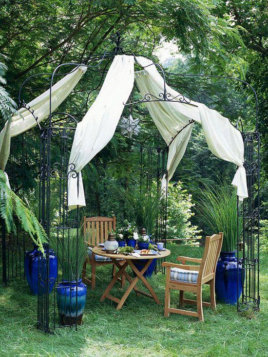 Простой и красивый вариант для любого сада: пустить вьющиеся растения по ажурной кованой беседке. Также ее можно украшать разнообразными драпировками