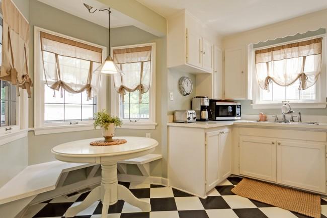 Легкие бежевые шторы на завязках хорошо смотрятся с кухней молочного цвета