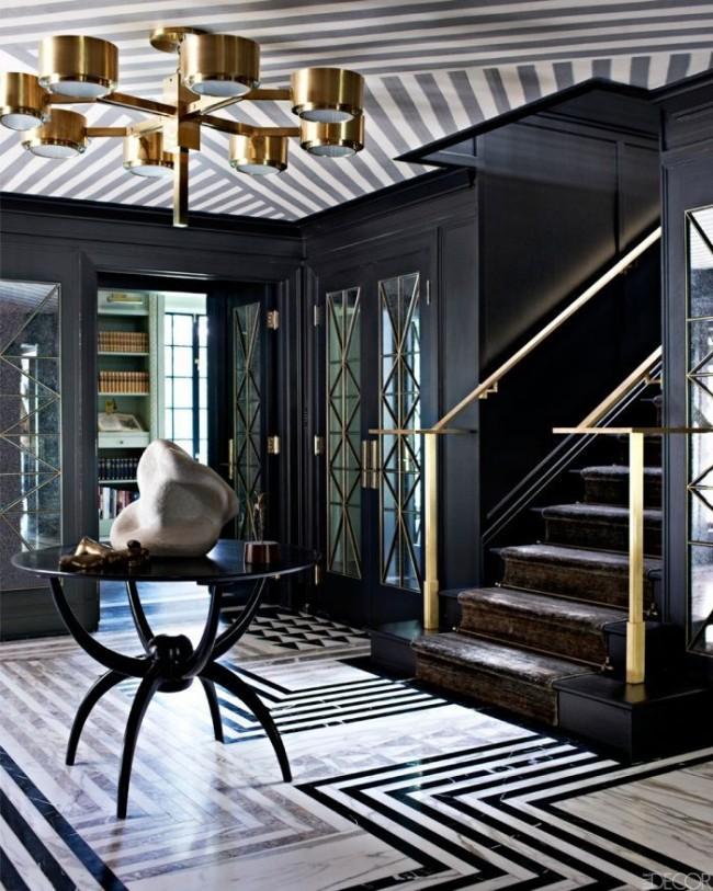 Геометрия на полу и потолке, черно-белая гамма, необычная люстра, лестница - все это выдает стиль арт-деко