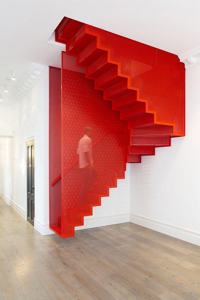 Лестница на второй этаж. Мгновенный заряд энергии при подъеме или спуске по металлической лестнице яркого красного цвета. Опора в этой сетчатой конструкции схожа с больцевой