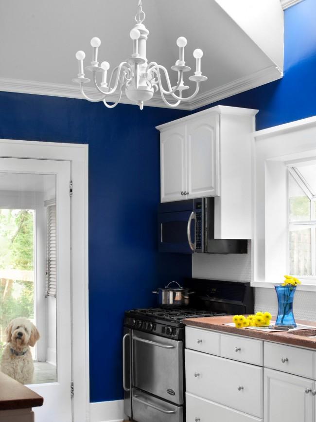 Классическая белая люстра отлично сочетается с пестрой синей окраской стен