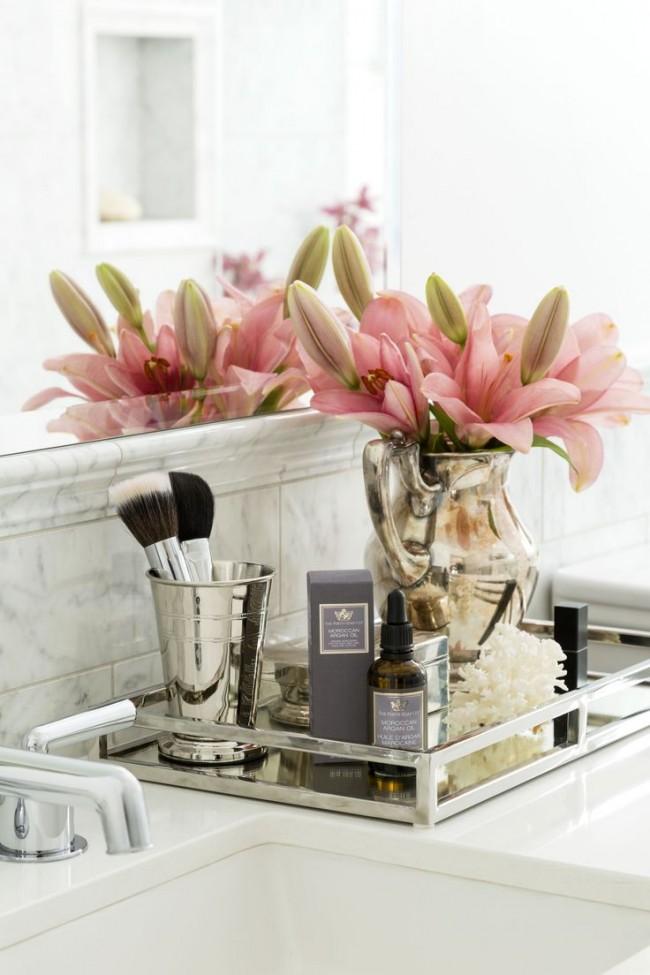 Красивые флакончики с косметикой, букетики цветов чудесно украсят ванную комнату женщины