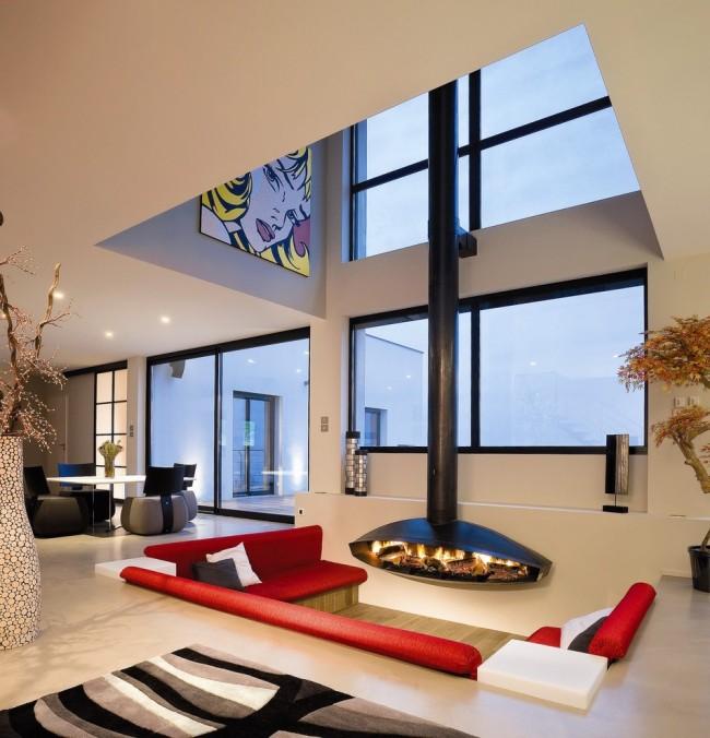 Экстравагантный камин и красный диван в современной гостиной