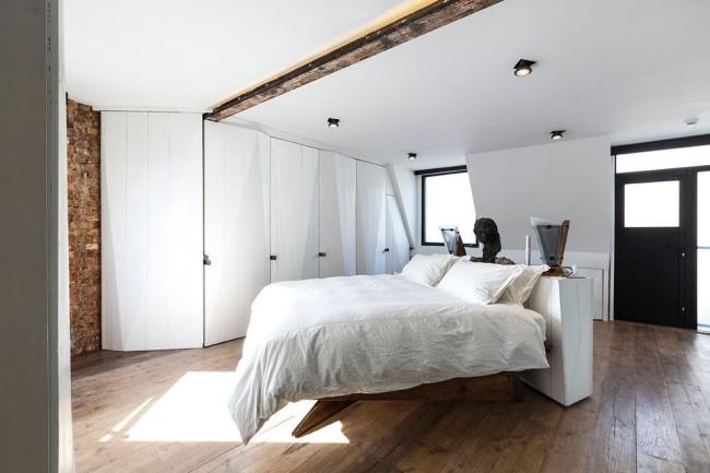 Светлую ламинатную доску дополняет каркас кровати, балка и кирпичная стенка